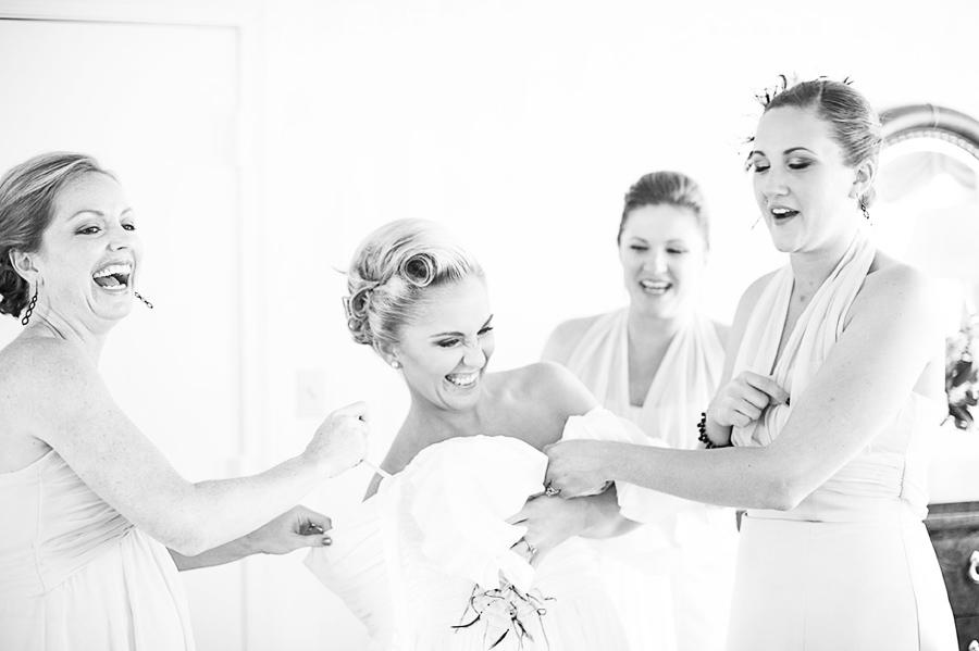 bridesmaid helping the bride dress
