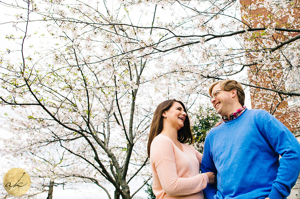 university of maryland college park spring engagement couple laughing standing under a flowering tree